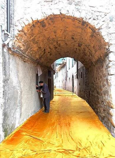 A local in the town of Sulzano part of the 100,000 square meters of shimmering dahlia-yellow fabric on the piers and pedestrian streets in Sulzano and Peschiera Maraglio (Photo_ Wolfgang Volz)